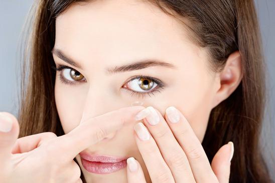 woman putting contact lens