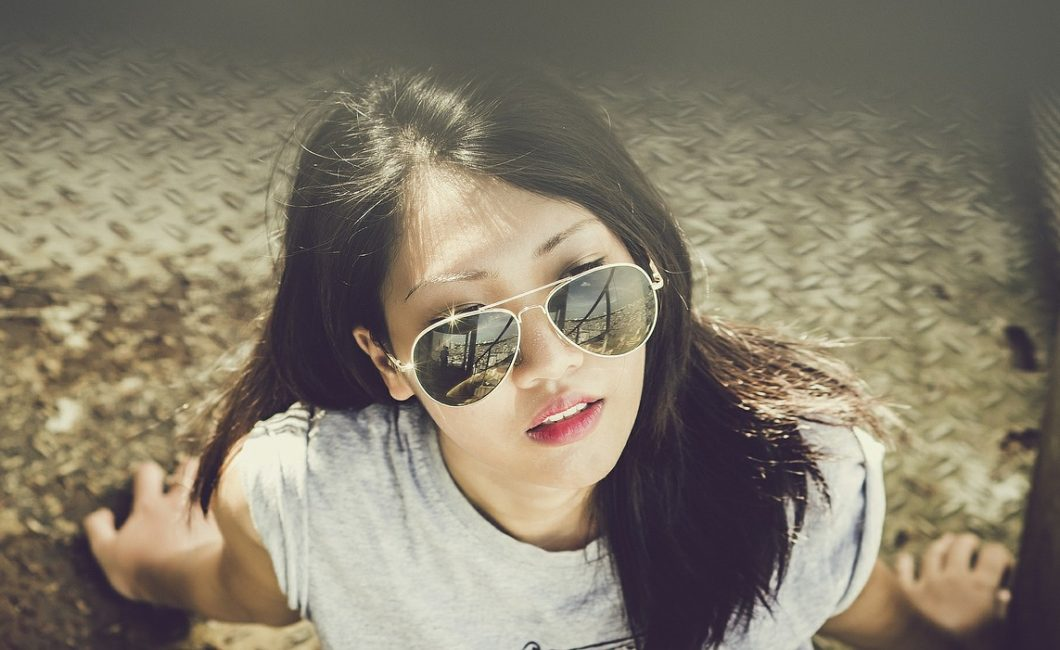 young woman in sunglasses in urban environment